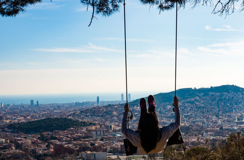 Rear view of woman swinging on rope swing against cityscape and sky