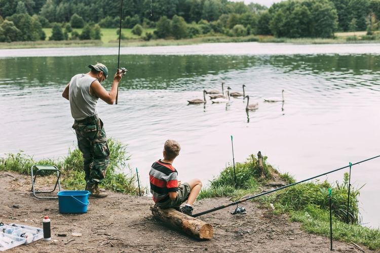 Rear view of men fishing in lake