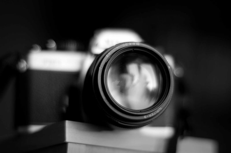 Close-up of camera lens against blurred background