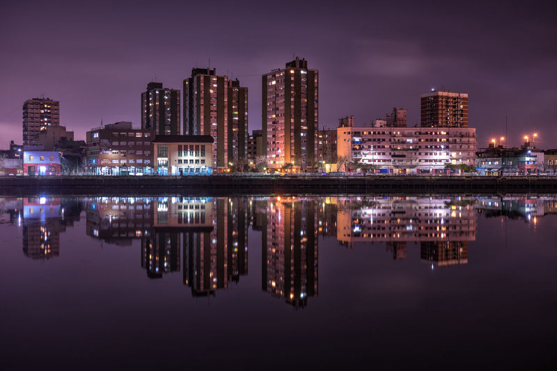 Illuminated buildings by calm river with reflection at night