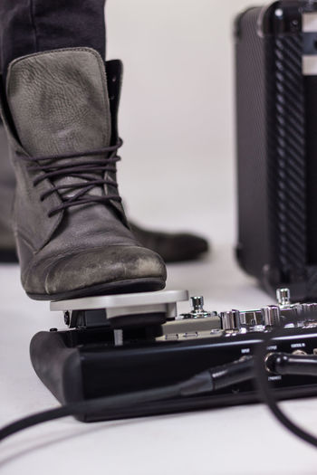 Low section of man on pressing guitar effects pedal
