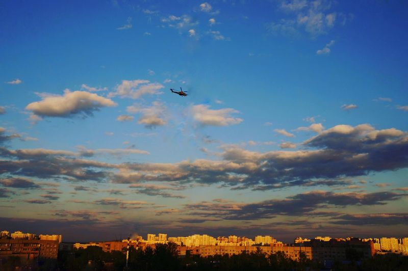 Airplane flying over cityscape against sky