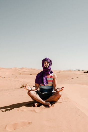 A man in a turban meditating on a dune in the sahara desert