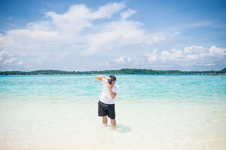 Man photographing using camera in sea against cloudy sky