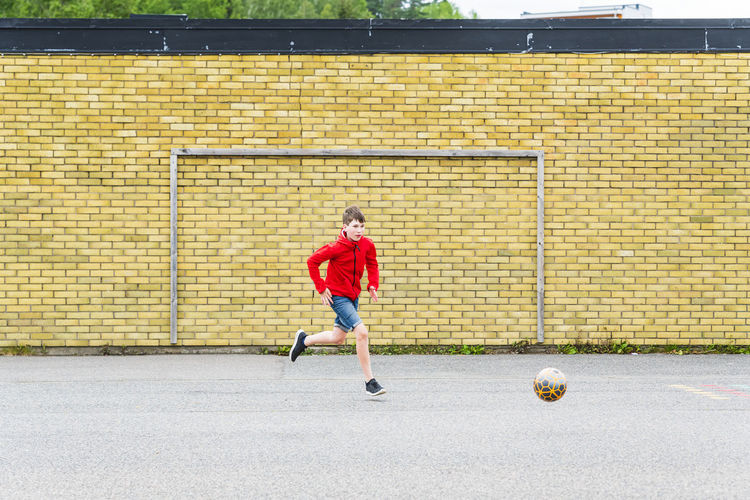 Full length of boy playing soccer ball on stone wall