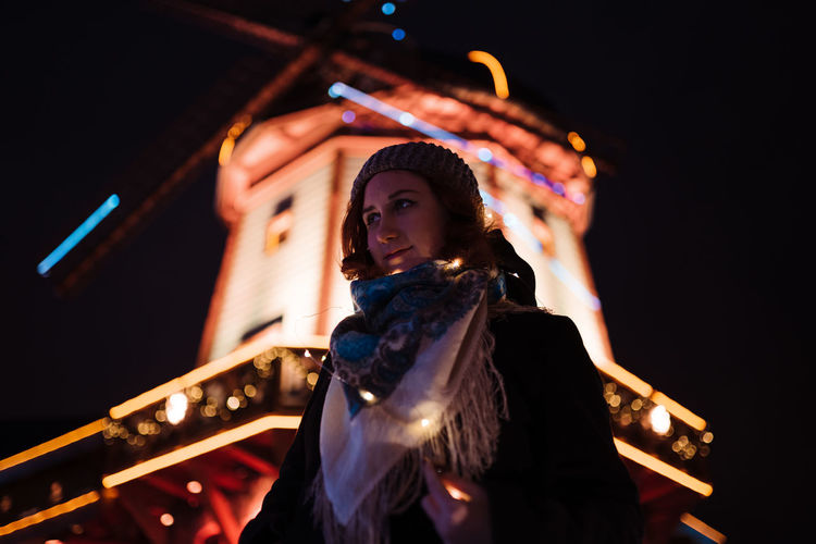Low angle view of woman standing at night