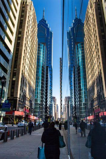 Rear view of modern buildings in city against blue sky