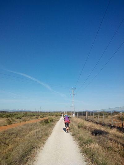 Rear View Of Man Walking On Footpath At Camino De Santiago