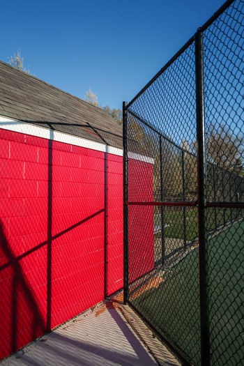 Red storage shed and black fence around tennis court