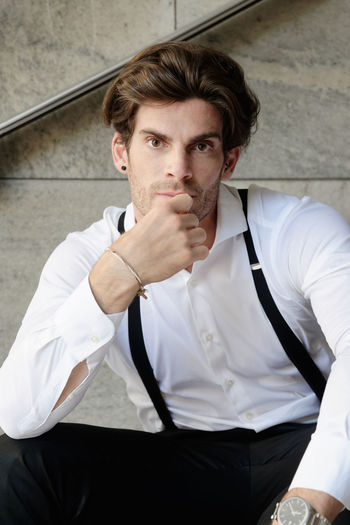 Portrait of man wearing suspenders while sitting on steps