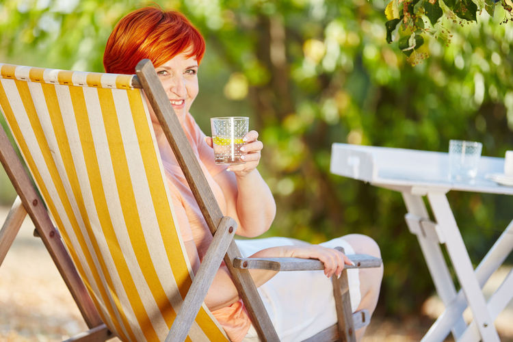Portrait Of Woman Holding Drinking Glass While Sitting On Deck Chair
