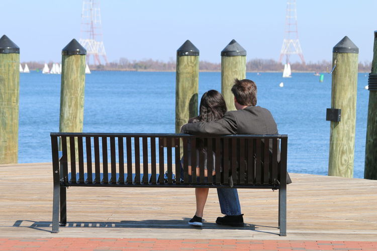Rear view of couple sitting at riverbank against clear sky