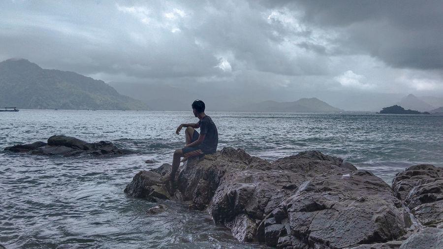 Man sitting on rock at beach against sky