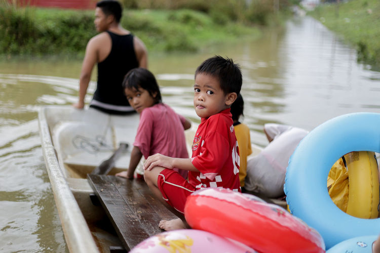 flood victims at kelantan Flood Victim Boys Casual Clothing Childhood Day Elementary Age Full Length Girls Lake Leisure Activity Lifestyles Mother Nature Oar Outdoors Raft Real People Sitting Son Togetherness Water