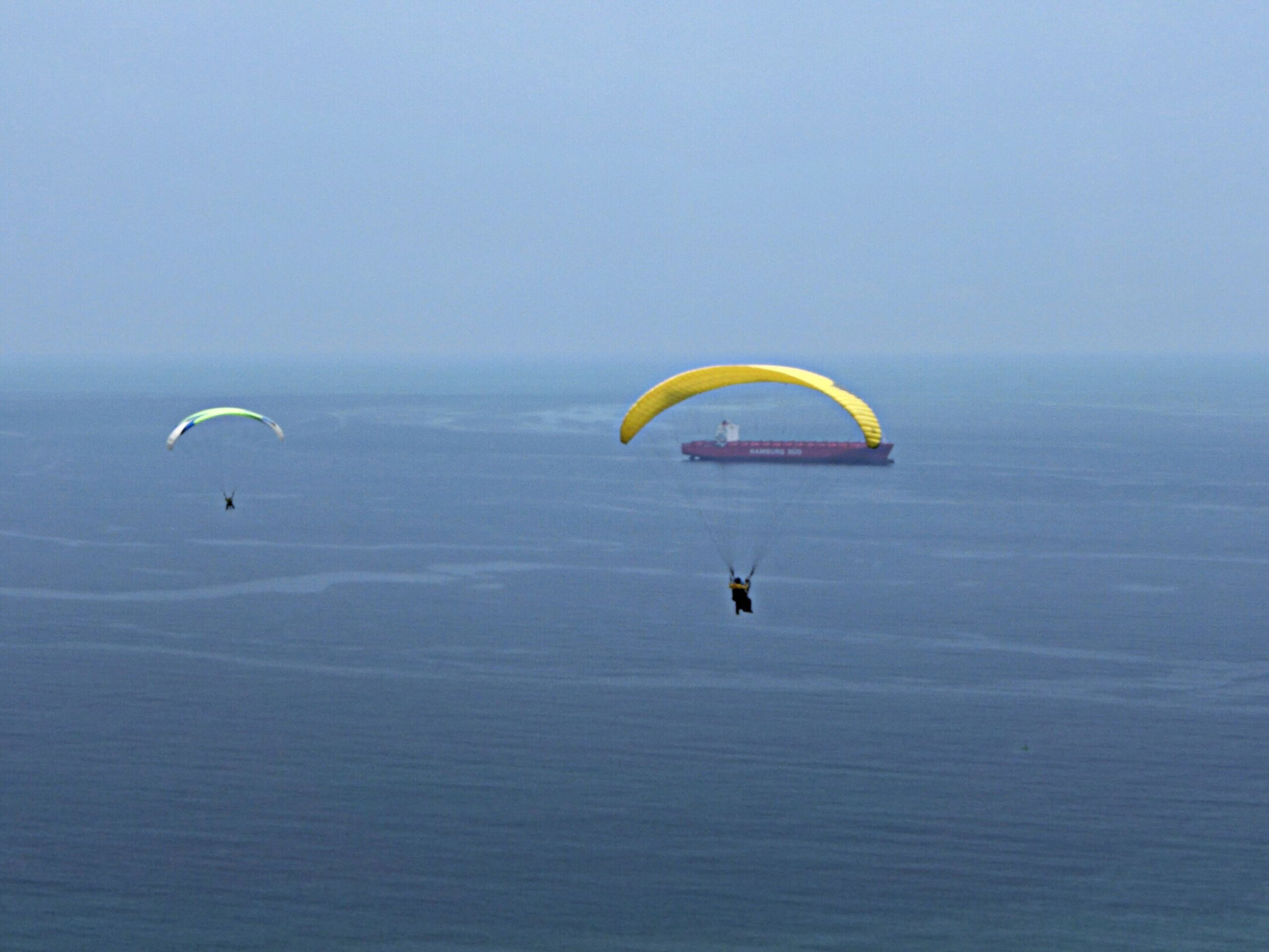 extreme sports, parachute, adventure, sport, sea, paragliding, mid-air, leisure activity, flying, water, waterfront, tranquility, scenics, tranquil scene, copy space, lifestyles, unrecognizable person, horizon over water