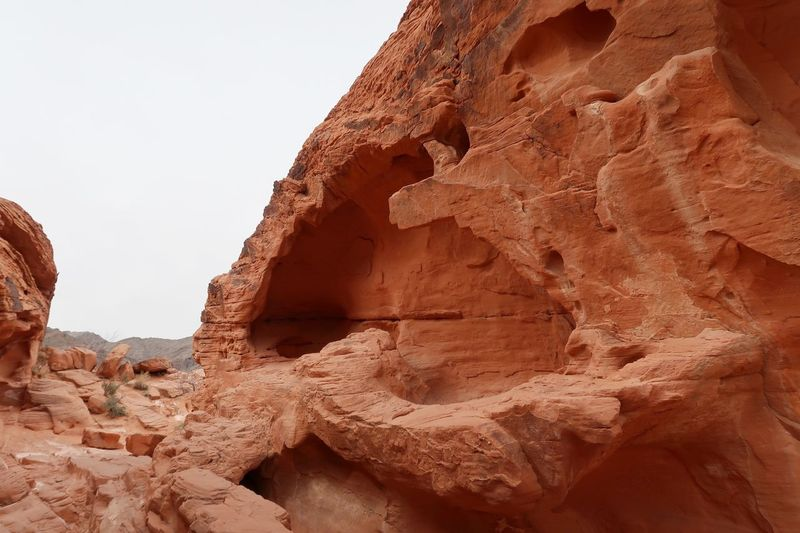 Side view of massive orange rock formation and a cave-like section Sand Stone Formations Valley Of Fire State Park Rock - Object Rock Formation Geology Sand No People Nature Day Arid Climate Physical Geography Beauty In Nature Scenics Sky Sand Dune Outdoors Desert Go Higher