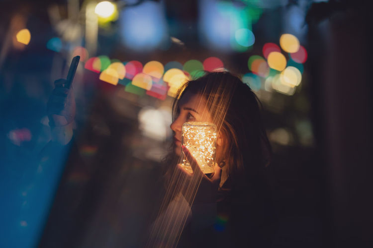 Young woman holding illuminated jar and mobile phone at night