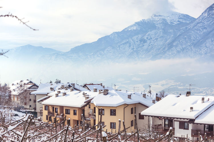 High angle view of houses and snowcapped mountains against sky