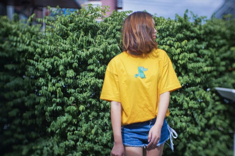 Rear view of woman standing against yellow plants