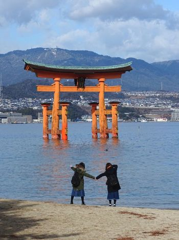 Real People Rear View Lifestyles Leisure Activity Architecture Two People Built Structure Sky Outdoors Water Standing Nature Architectural Column Day Full Length Beauty In Nature Men Cloud - Sky Connection Women Friendship Friends Japan TORII Miyajima