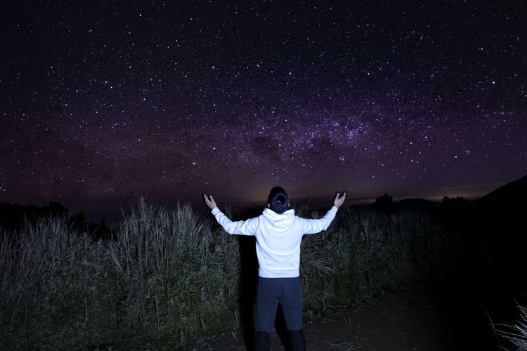 Rear view of man with arms outstretched standing against star field