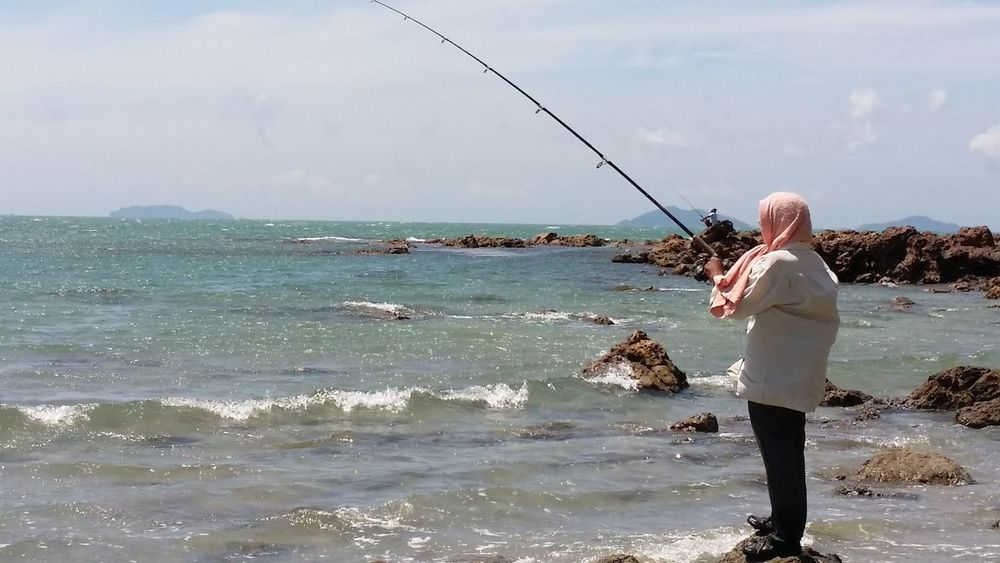A man fishing at noon Adult Beach Day Fishing Fishing Pole Full Length Horizon Over Water Leisure Activity Nature Noon One Person Outdoors People Real People Rear View Sea Sky Standing Village People Water