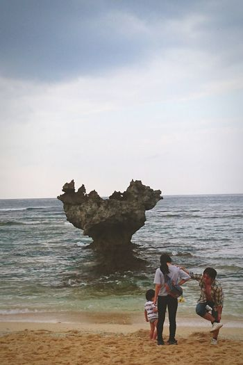 A family of three standing in front of a heart-shaped rock.Beach Sea Sand Horizon Over Water Coastline Bonding Togetherness Water Nature Family Heart