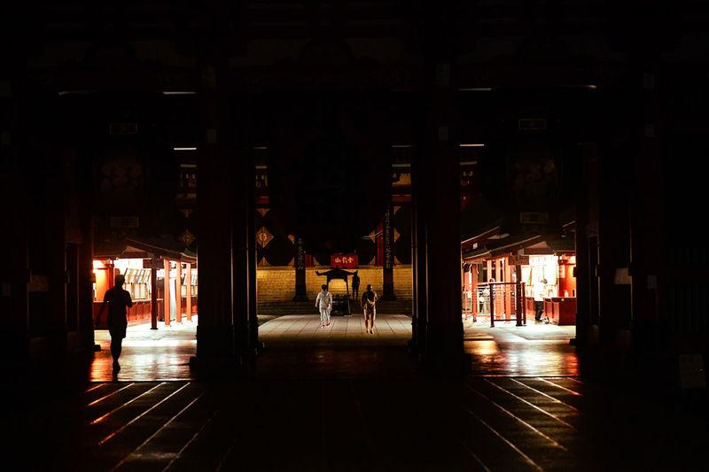 Silhouette people on illuminated street amidst buildings at night