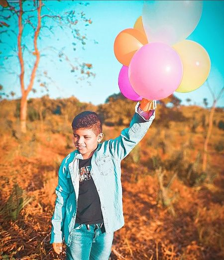 Full length of a man holding colorful balloons