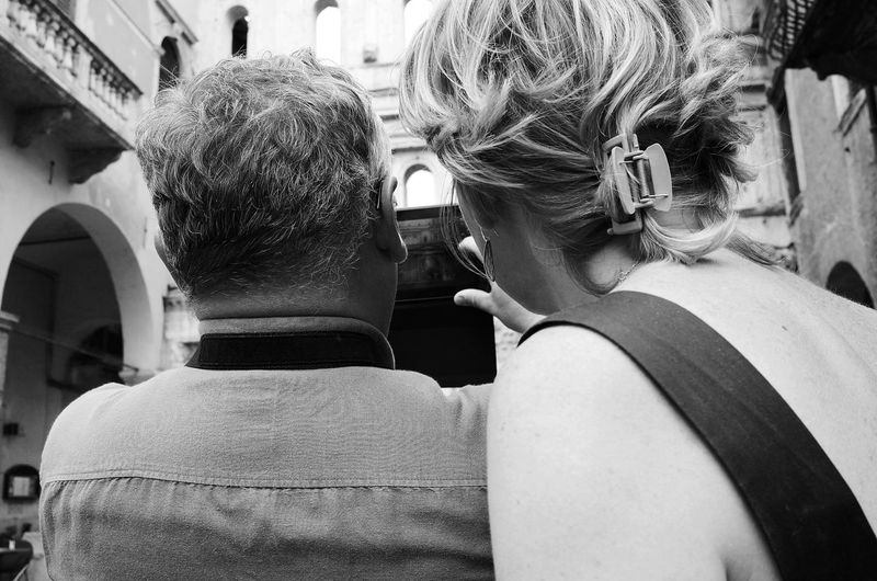Rear view of man and woman clicking photograph with smart phone