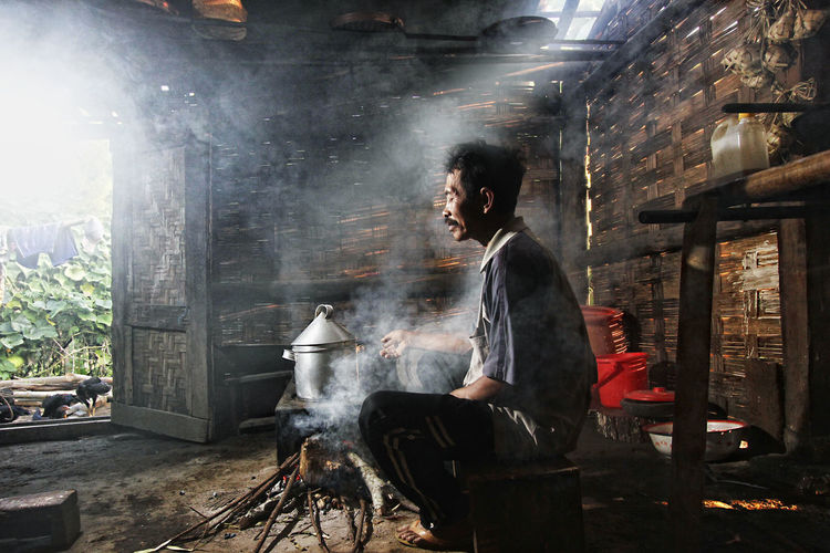Side view of man sitting by wood burning stove in hut