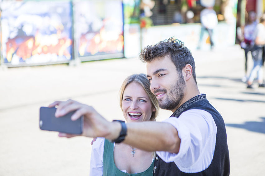 A young German couple pose in front of the camera whilst making at selfie at the Octoberfest festival in Munich, Germany Bavarian Girl Bavarian Man Bavarian Style Couple Dirndl Enjoyment Festival Freedom German Style Germany In Love Lederhosen Munich München Octoberfest Party Relationship Selfie Style Theresienwiese Tracht Wiesn Young Young Couple Youth