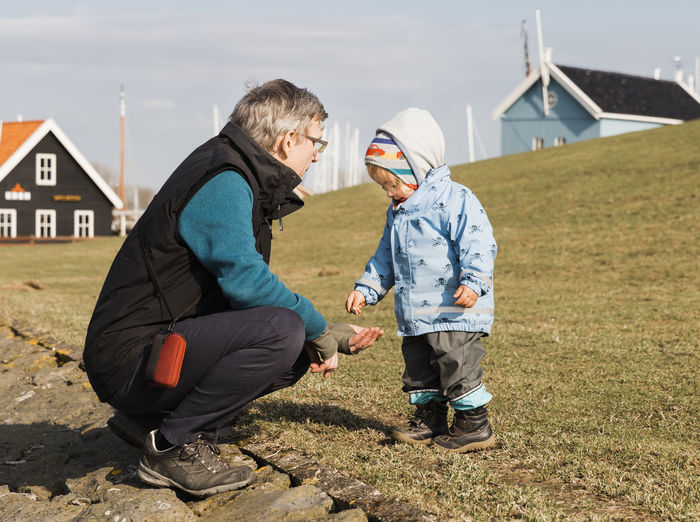 Grandfather With Granddaughter Wearing Warm Clothing On Grassy Field