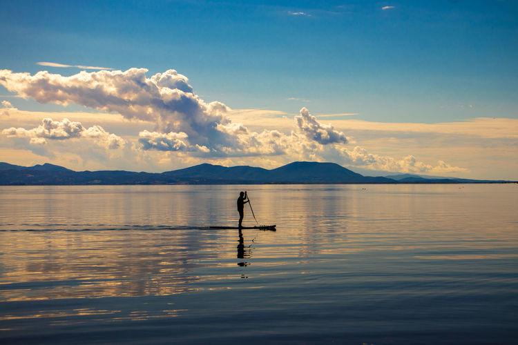 Silhouette man paddleboarding on lake during sunset