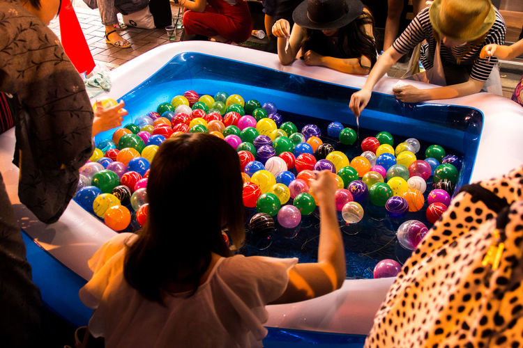 High Angle View Of People Playing With Colorful Balloons In Wading Pool