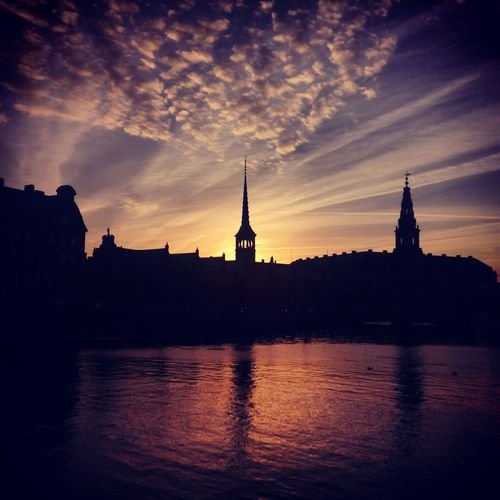 Silhouette buildings by calm river against cloudy sky