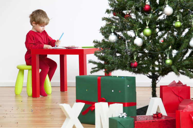 Boy with umbrella on table in christmas tree