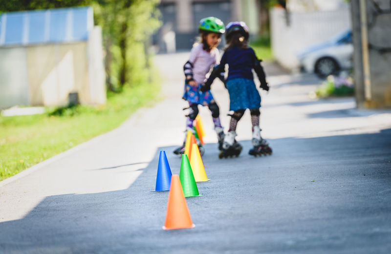 Children learning to roller skate on the road with cones. Twin girls are practising safe roller skating on a home driveway road wearing protective gear - helmets, knee, elbow and hand protectors or pads. Children Home IDENTICAL TWINS Recreation  Road Roller Active Active Lifestyle  Day Driveway Girl Helmet Outdoors Protection Protection Gear Real People Roller Blades Roller Skate Girl Roller Skating Roller Skating ! Rollerskating Skates Skating Sports Twin