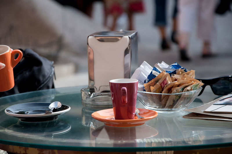 Coffee cup with sugar packets on table