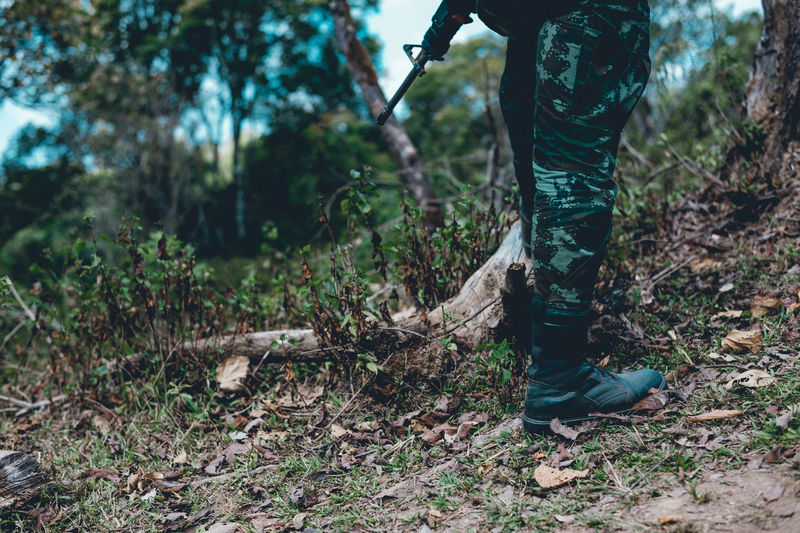 Low section of soldier standing by plants