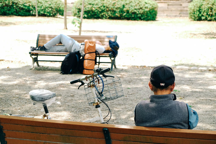 Men Sitting And Lying On Benches At Park