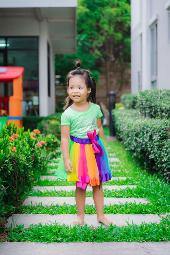 Smiling girl standing on footpath