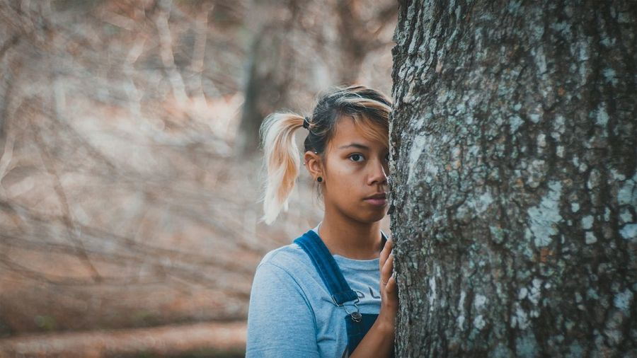 Portrait of young woman standing by tree