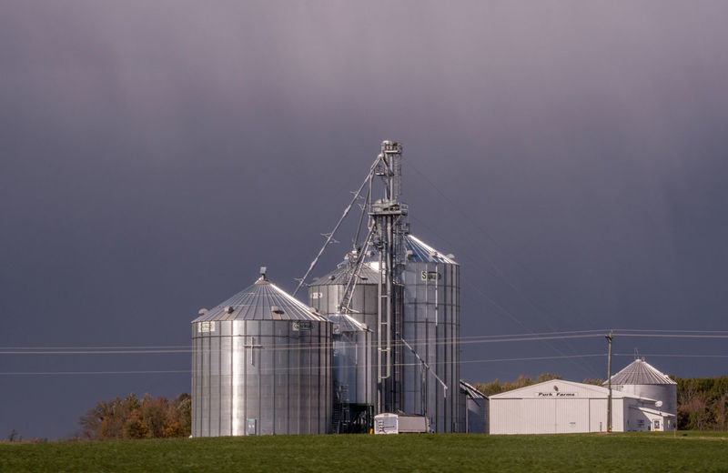 Modern farm shines with storm clouds creating dramatic shadows on the metal silos