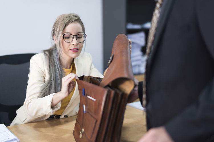 Woman checking man bag on table in office