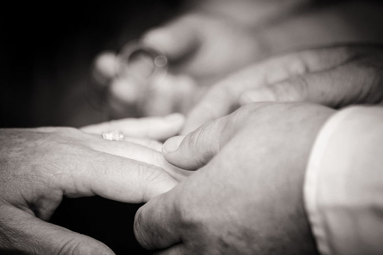 Cropped Hand Of Bride Putting Ring On Bridegroom During Wedding Ceremony