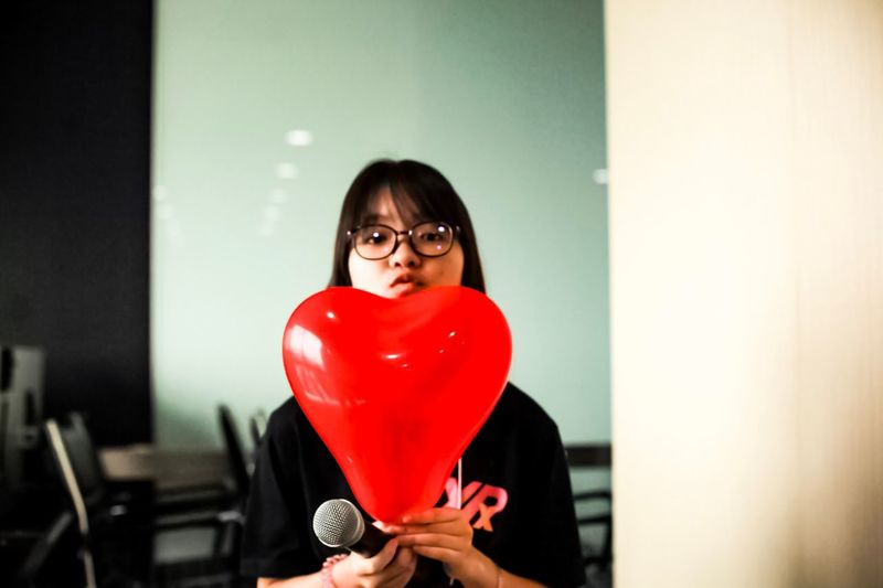 Young Woman Holding Heart Shaped Balloon