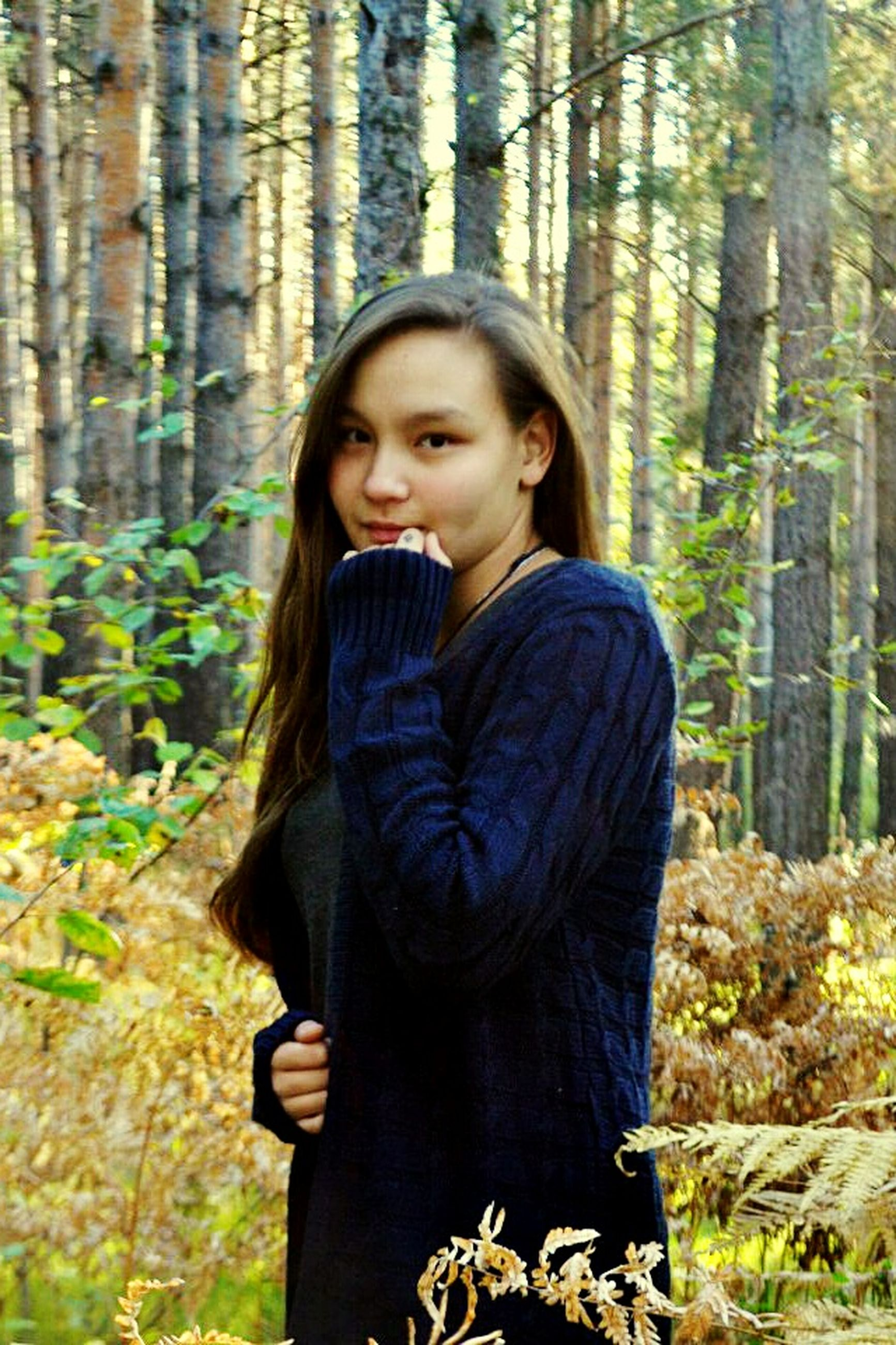 tree, portrait, person, forest, looking at camera, casual clothing, tree trunk, lifestyles, front view, standing, leisure activity, waist up, three quarter length, young adult, focus on foreground, smiling, nature, childhood