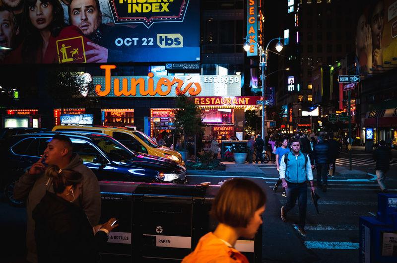 People on illuminated city street at night