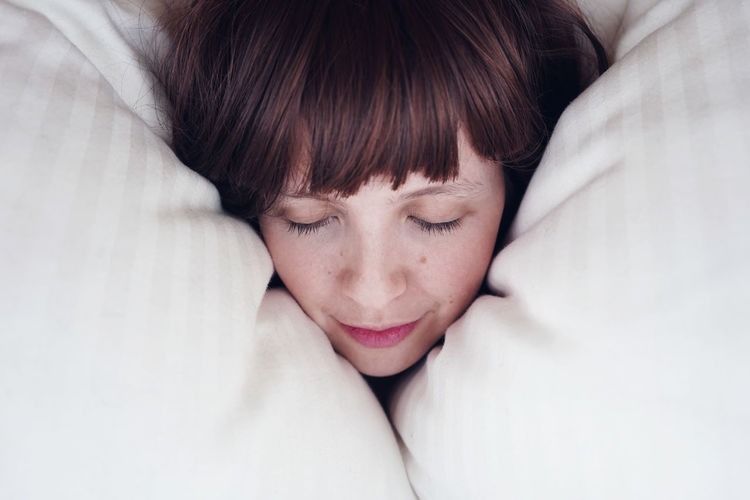 Close-Up Of Young Woman Sleeping On Bed At Home